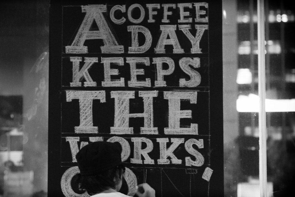 Feat - Anomali Coffee - Working on a chalk signboard